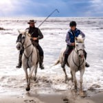 cowboy with Camargue horse on beach on France riding holiday by globetrotting