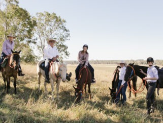 horses and riders resting in field rainbow beach horse riding holiday by globetrotting