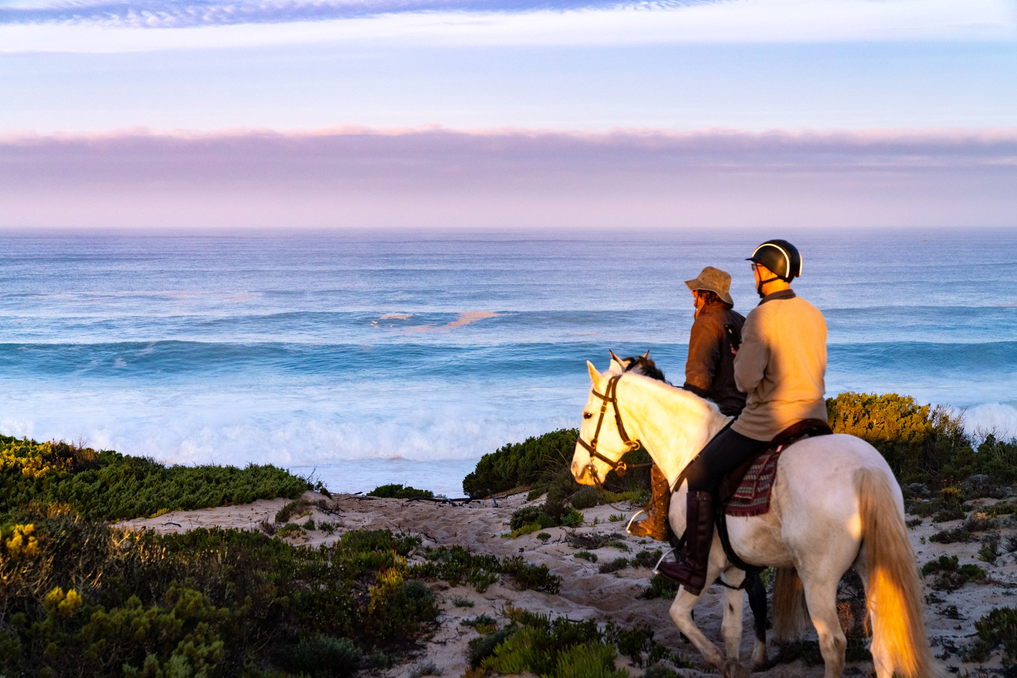 riders on beach sand dunes at sunset portugal horse riding holiday by globetrotting