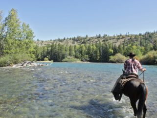 rider crossing river horse riding holiday canada by globetrotting